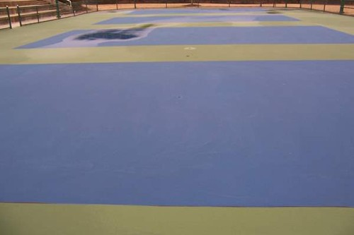 Multiple coats of textured acrylic is applied to the 36' tennis court playing area (blue) and overru