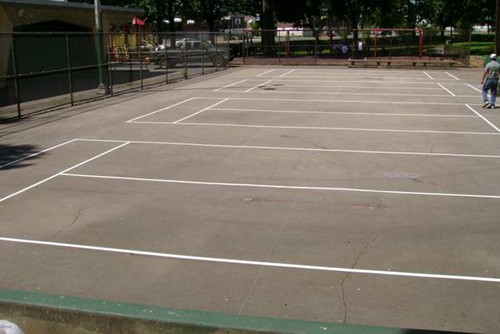 Four 36' tennis courts on an old outdoor basketball court in a park.
