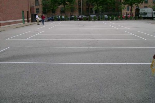 Four 36' tennis courts on a blacktop surface in a city park.