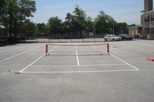 Four 36' tennis courts on a blacktop surface at an elementary school.